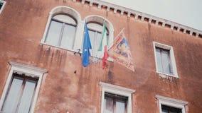 Schöne steadicam Froschperspektive des alten Amtsgebäudes mit drei wellenartig bewegender Flaggen EU, Italien und Venedig auf der stock video