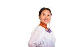 Schöne stehende tragende traditionelle Andenbluse der jungen Frau und rote Halskette, Drehenkopf, der in Richtung der Kamera blic Lizenzfreie Stockfotos