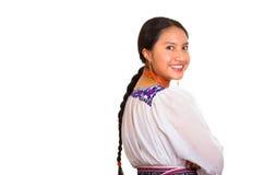 Schöne stehende tragende traditionelle Andenbluse der jungen Frau und rote Halskette, Drehenkopf, der in Richtung der Kamera blic Stockfotos