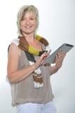 Schöne Stellung herauf die blonde ältere Frau, die mit Tablet-PC arbeitet Stockfotos