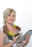 Schöne Stellung herauf die blonde ältere Frau, die mit Tablet-PC arbeitet Lizenzfreie Stockfotos