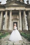 Schöne stilvolle blonde Braut, die nahe altem Schloss aufwirft Stockfotos