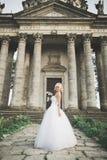 Schöne stilvolle blonde Braut, die nahe altem Schloss aufwirft Lizenzfreie Stockfotografie