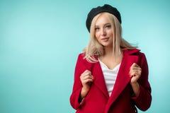 Schöne stilvolle blonde Frau, die roten Mantel und schwarzes Barett trägt Stockbild