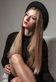 Schöne stilvolle Frau mit dem blonden langen Haar im schwarzen Kleid und im Hut Stockfoto