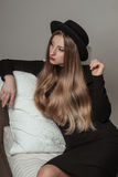 Schöne stilvolle Frau mit dem blonden langen Haar im schwarzen Kleid und im Hut Lizenzfreies Stockbild