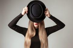 Schöne stilvolle Frau mit dem blonden langen Haar im schwarzen Kleid und im Hut Lizenzfreie Stockfotografie