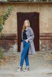 Schöne stilvolle junge Frau Blue Jeans eines in den modischen Schuhen der warmen Schals und gemütlichen im Mantel, die allein geg Stockbilder
