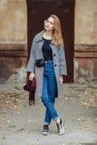 Schöne stilvolle junge Frau Blue Jeans eines in den modischen Schuhen der warmen Schals und gemütlichen im Mantel, die allein geg Stockfoto
