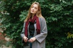 Schöne stilvolle junge Frau in einem modischen gemütlichen Mantel der warmen Schalblue jeans, der allein gegen grünes Laub in der Lizenzfreies Stockbild
