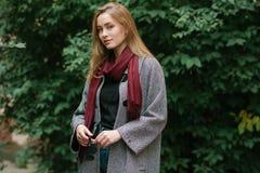 Schöne stilvolle junge Frau in einem modischen gemütlichen Mantel der warmen Schalblue jeans, der allein gegen grünes Laub in der Lizenzfreie Stockfotografie