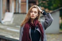 Schöne stilvolle junge Frau in einem modischen gemütlichen Mantel der warmen Schalblue jeans, der allein gegen verlassenes Yard i Stockbilder