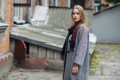 Schöne stilvolle junge Frau in einem modischen gemütlichen Mantel der warmen Schalblue jeans, der allein gegen verlassenes Yard i Stockfotos