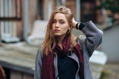 Schöne stilvolle junge Frau in einem modischen gemütlichen Mantel der warmen Schalblue jeans, der allein gegen verlassenes Yard i Stockbild
