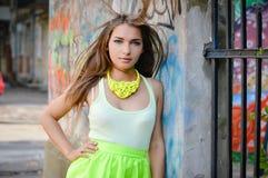 Schöne stilvolle Modefrau an der Graffitiwand in der Stadt mit dem Fliegenhaar Stockfoto
