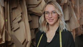 Schöne stilvolle Näherin in einem schwarzen Hemd überprüft nähende Zeichnungsmuster stock video footage