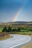 Schöne Straße mit Regenbogen im blauen Himmel, Südinsel, Neuseeland Lizenzfreie Stockfotografie