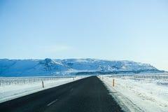 Schöne Straße mit schneebedecktem Berg während des Winters in Island Stockfoto