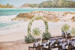 Schöne Strandhochzeits-Blumen-Bogeneinstellung für Heiratsort mit panoramischem Meerblick stockfotos
