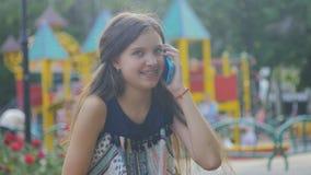 Schöne strenge Jugendliche, die oben auf Handyabschluß, gegen Grün des Sommerparks spricht stock video