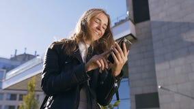 Schöne Studentin, die das digitale Gerät aufpasst die sozialmassenmedien, interessante Nachrichten auf App beim Gehen lesend verw stock footage