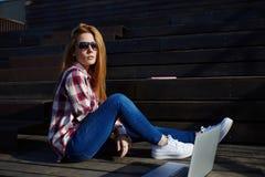 Schöne Studentin, die für Vorträge bei ihr Netzbuch auf dem Campus verwenden sich vorbereitet lizenzfreie stockfotografie