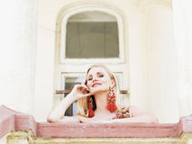 Schöne suducive nette blonde Frau, die vom Balkon schaut Lizenzfreie Stockfotografie