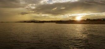 Schöne Szene des Panoramas des Sonnenuntergangs am Meer, an den Wolken und am großen Berg im Hintergrund, Licht des Sonnenunterga Lizenzfreie Stockfotos