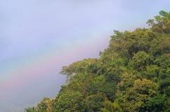 Schöne Szene von Regenbogen über grünem Berg mit blauem Himmel im Herbst Lizenzfreies Stockbild