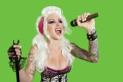 Schöne tätowierte Frau, die mit Mikrofon über grünem Hintergrund singt Lizenzfreie Stockbilder
