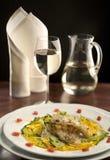 Schöne Tabelle mit einer Platte von gegrillten Fischen und von Glas Whit lizenzfreie stockfotos