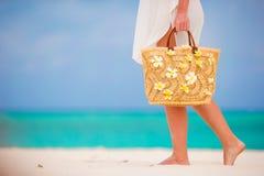 Schöne Tasche der Nahaufnahme mit Frangipaniblumen und -Sonnenbrille auf weißem Strand in den weiblichen Händen Lizenzfreie Stockfotografie