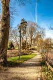 Schöne teilweise Ansicht des Proosdij-Parks mit einem Erdweg nahe bei dem Teich mit Bäumen stockfoto