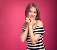 Schöne toothy lächelnde blonde Frau in gestreiftem Kleid mit den Händen Stockfoto