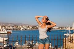 Schöne touristische Frau auf dem alten Schloss auf Mittelmeerküste Paphos, Zypern Helles Sonnenunterganglicht stockfotografie