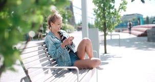 Schöne tragende Denimjacke der jungen Frau, die am Telefon in einem Stadtpark während des sonnigen Tages schreibt Lizenzfreies Stockfoto