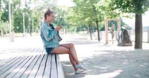 Schöne tragende Denimjacke der jungen Frau, die am Telefon in einem Stadtpark während des sonnigen Tages schreibt Lizenzfreie Stockfotografie