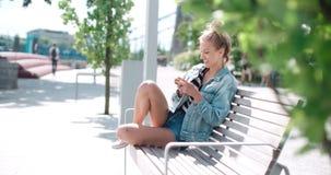 Schöne tragende Denimjacke der jungen Frau, die am Telefon in einem Stadtpark während des sonnigen Tages schreibt Lizenzfreie Stockbilder