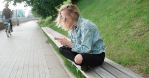 Schöne tragende Denimjacke der jungen Frau, die am Telefon während des sonnigen Tages schreibt Stockbilder