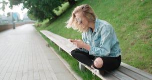 Schöne tragende Denimjacke der jungen Frau, die am Telefon während des sonnigen Tages schreibt Lizenzfreies Stockbild