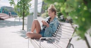 Schöne tragende Denimjacke der jungen Frau, die am Telefon während des sonnigen Tages schreibt Lizenzfreies Stockfoto