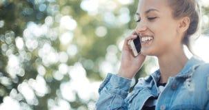 Schöne tragende Denimjacke der jungen Frau, die am Telefon während des sonnigen Tages spricht Stockbilder