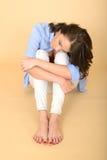 Schöne traurige deprimierte und verärgerte junge Frau, die auf dem Boden sitzt Stockfoto