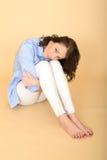 Schöne traurige deprimierte und verärgerte junge Frau, die auf dem Boden sitzt Stockfotos