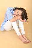 Schöne traurige deprimierte und verärgerte junge Frau, die auf dem Flo sitzt Lizenzfreies Stockbild