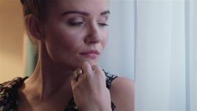 Schöne traurige junge Frau, die nahe dem Fenster steht stock video
