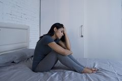 Schöne traurige und deprimierte lateinische Frau, die zu Hause auf Bett f sitzt Lizenzfreie Stockfotos