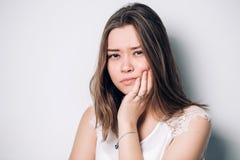 Schöne traurige unglückliche Frauengefühlschmerz auf ihren Zähnen lokalisiert auf weißem Hintergrund lizenzfreie stockfotos
