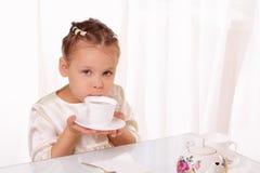 Schöne trinkende Tasse Tee des kleinen Mädchens Lizenzfreies Stockbild