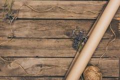Schöne Trockenblumen, Kraftpapier und Seil vereinbarten auf Holztisch Stockfoto